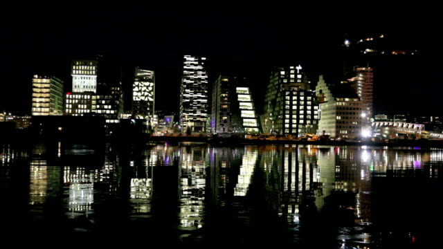 Skyline of Oslo at night reflecting in water.