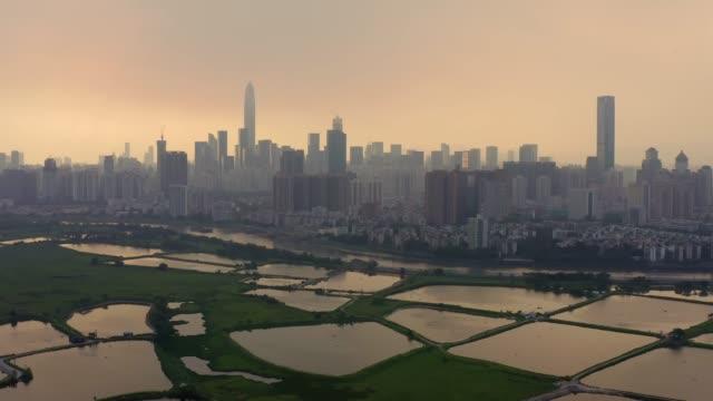 stockvideo's en b-roll-footage met skyline of shenzhen city, china at twilight. viewed from hong kong border - hong kong