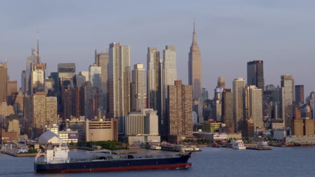 a skyline of the west side of manhattan a oil tanker and ferry cross the frame. - harbour stock videos & royalty-free footage
