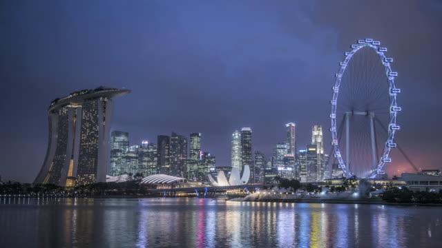 ws t/l skyline showing marina bay sands and singapore flyer at dusk / singapore - singapore flyer stock videos and b-roll footage