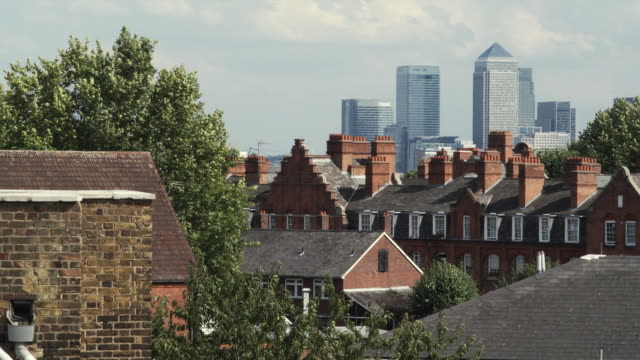 ws skyline view of roofs with canary wharf business district in background / london, united kingdom - roof stock videos & royalty-free footage