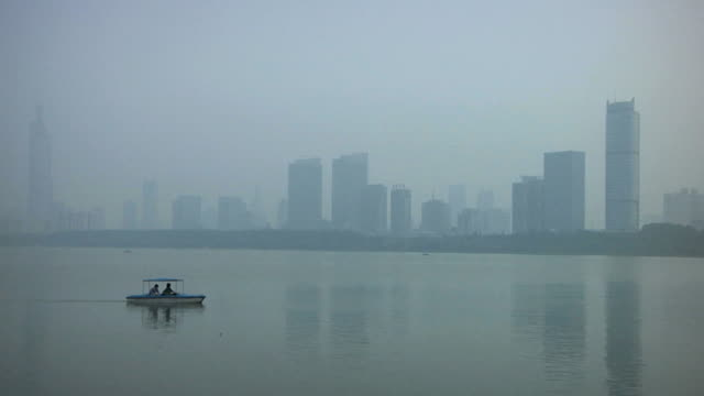 ws skyline with small boat in foreground, extreme pollution / nanjing, jiangsu, china - nanjing stock videos & royalty-free footage