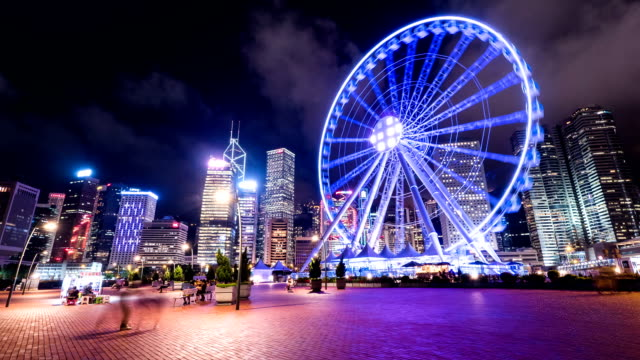 skyline,ferry wheel,tourists and modern buildings in hong kong at night,time lapse. - wheel stock videos and b-roll footage