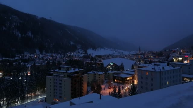 skylines of snow topped buildings at night in davos, switzerland on friday, jan. 13 congress center, the venue for the world economic forum - ナイトイン点の映像素材/bロール