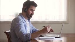 Skype teacher wearing headset looking at laptop screen making notes