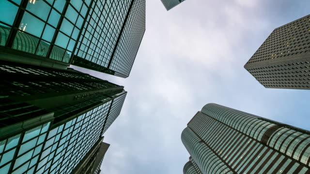 vidéos et rushes de gratte-ciel entassés des immeubles de grande hauteur avec le ciel et les nuages au-dessus de la tour, time lapse - zoom avant