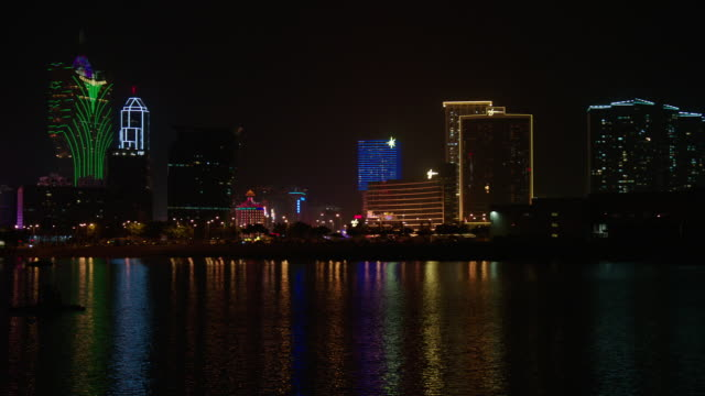 skyscraper hotels, casinos, resorts along waterfront w/ colorful lights reflecting in lake. - macao stock videos & royalty-free footage