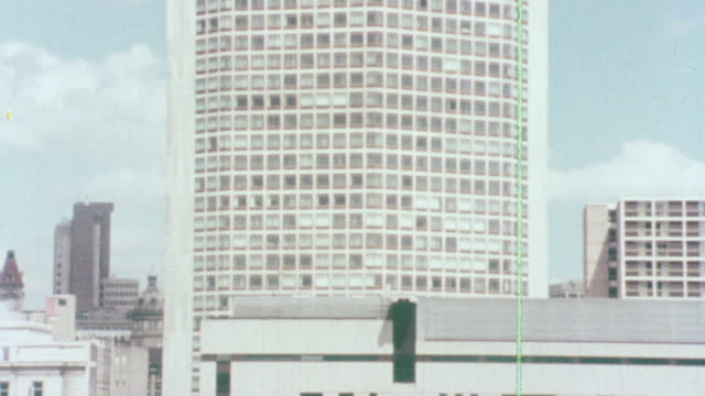 1976 MONTAGE Skyscraper rising above the city as a pedestrian is sitting in a city plaza / Birmingham, England, United Kingdom