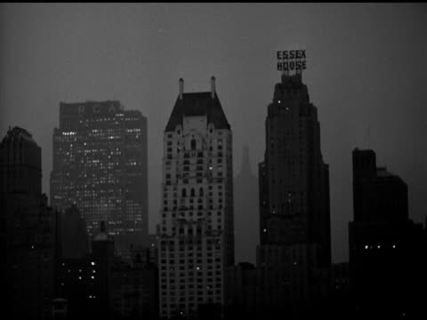 skyscrapers at south end of central park, rca building, essex house. on the air' lighted sign. - rca stock videos & royalty-free footage