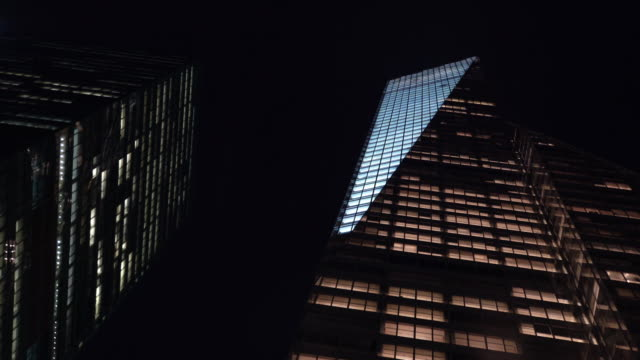 skyscrapers illuminated at night - skyscraper stock-videos und b-roll-filmmaterial
