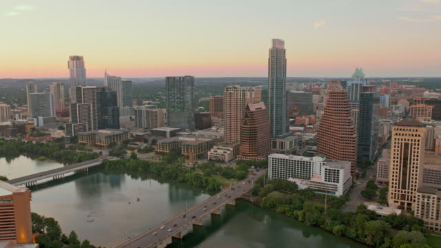 aerial skyscrapers in austin along the colorado river at sunset - gulf coast states stock-videos und b-roll-filmmaterial