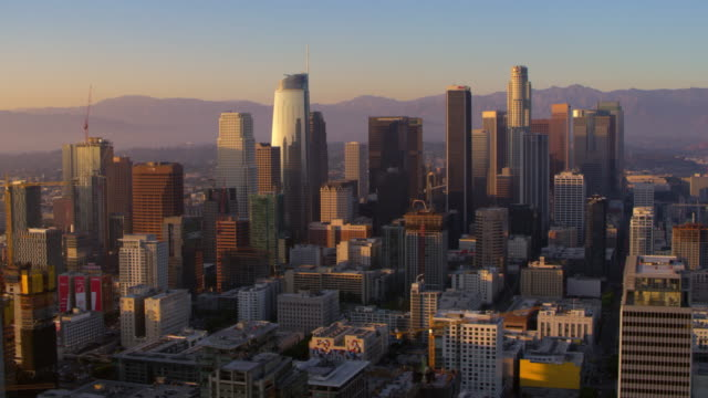 aerial skyscrapers in downtown los angeles at sunset - grandangolo tecnica fotografica video stock e b–roll
