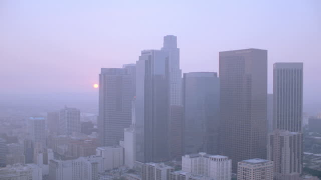 stockvideo's en b-roll-footage met skyscrapers in downtown los angeles rise up through the haze and smog during the golden-hour. - smog