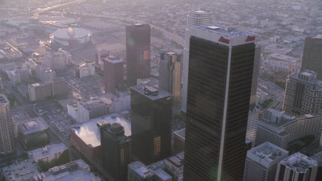 AERIAL Skyscrapers in the Financial District, including U.S. Bank Tower and Aon Center, urban sprawl and Staples Center sports arena beyond / Los Angeles, California, United States