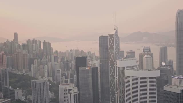 stockvideo's en b-roll-footage met skyscrapers in the hong kong city skyline at sunset. aerial drone view - hong kong