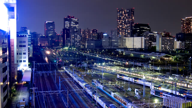 skyscrapers overlook a tokyo train yard. - shunting yard stock videos and b-roll footage
