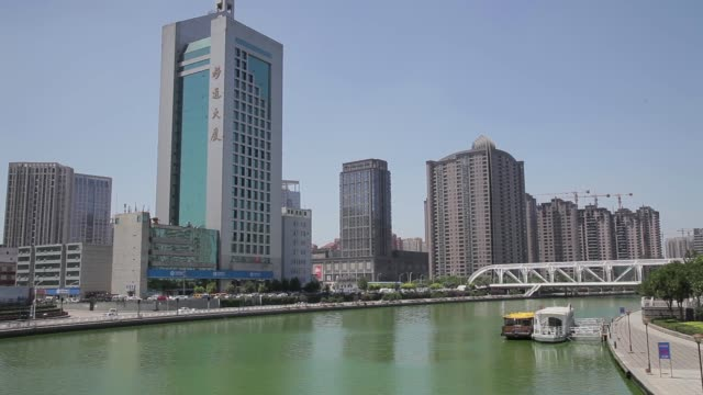skyscrapers reflect in the hai river in downtown tianjin, china. - hai river stock videos & royalty-free footage
