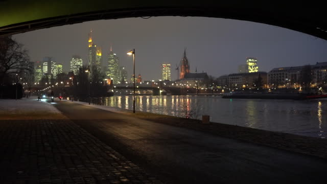 skyscrapers stand illuminated in the financial district beyond the river main in frankfurt germany on thursday jan 24 2019 ecb president mario... - ヘッセン州点の映像素材/bロール