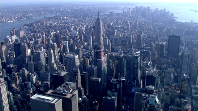 skyscrapers surround the empire state building in new york city. - empire state building stock videos & royalty-free footage