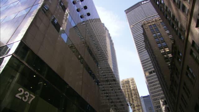 skyscrapers tower over a street in manhattan. - manhattan video stock e b–roll