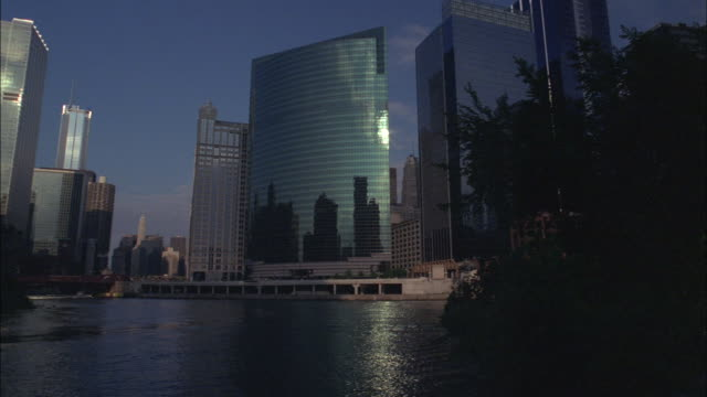 skyscrapers tower over the river in chicago. - chicago 'l' stock videos & royalty-free footage