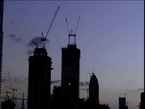 skyscrapers under construction silhouetted at dusk dubai - erezione video stock e b–roll