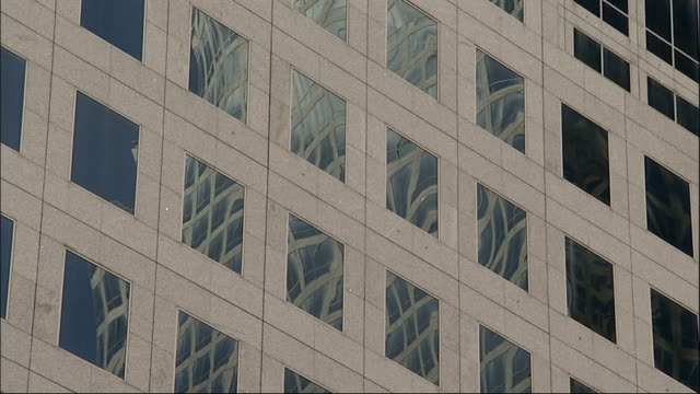 A skyscraper's windows reflect an adjacent building in New York City. Available in HD.