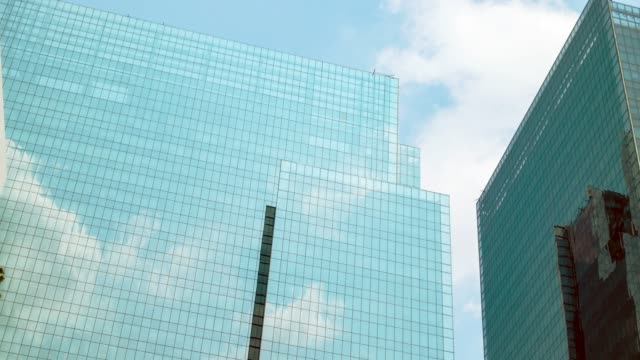 skyscrapers with clouds reflected in glass walls. - angle stock videos & royalty-free footage