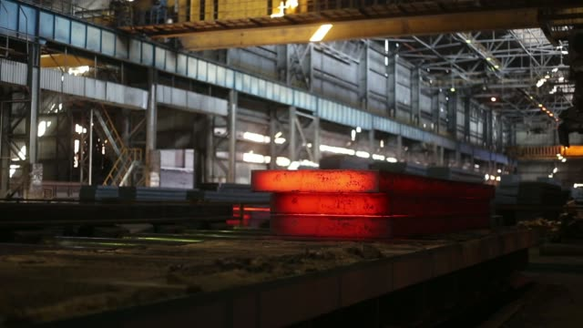 slabs of red hot steel sit in a cooling facility at the alchevsk iron steel works pjsc metallurgical plant also known as alchevskiy metalurgiyniy... - iron ore stock videos & royalty-free footage