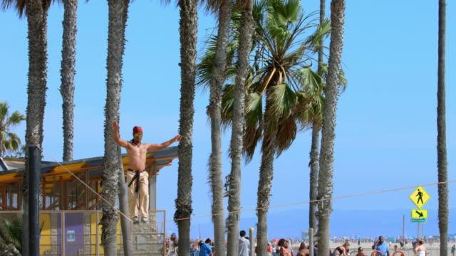 slackliner walker balancing on tightrope in santa monica beach, los angeles, california, 4k, from raw file - tightrope walking stock videos & royalty-free footage