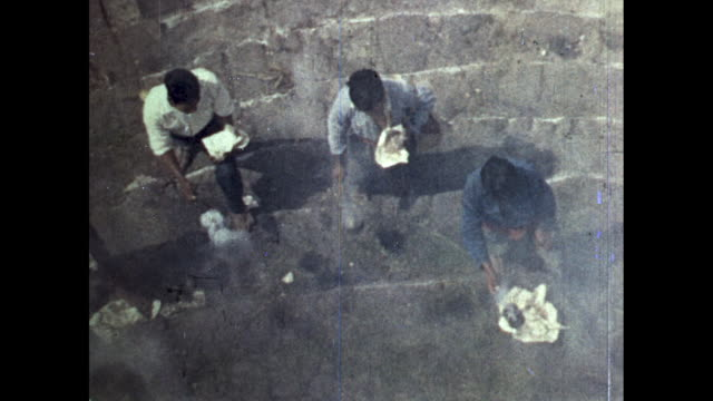 vidéos et rushes de slant shot of young men swinging pot emitting smoke people burning at bottom of stairs aerial shot of young men swinging smoking pot - répandre