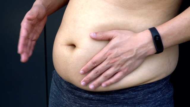 vídeos de stock e filmes b-roll de slapping fat on stomach - overweight
