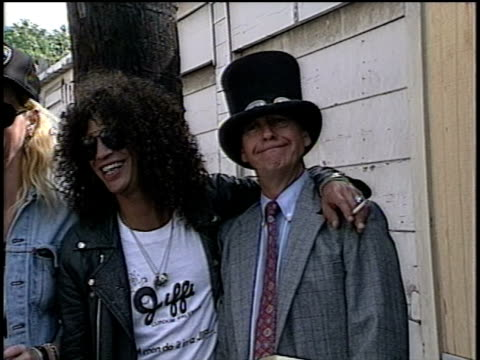 Slash is getting his top hat and giving it to Dick Clark to wear during a photo shoot