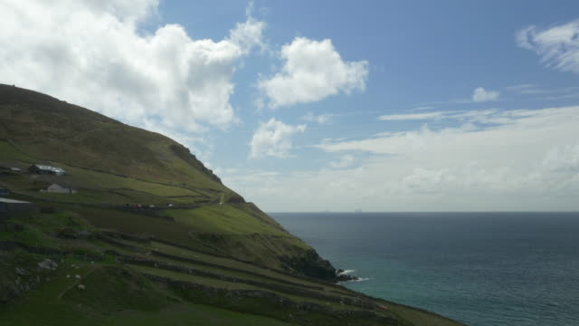 WS Slea Head Drive, Dingle Peninsula, cars rounding curve on narrow road next to Atlantic Ocean, Irish countryside, clouds