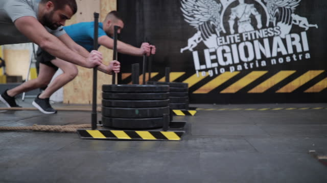 sled push training drill - pushing stock videos & royalty-free footage
