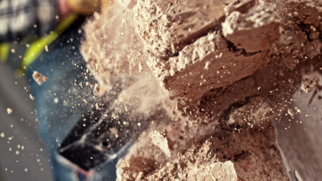 slo mo sledge hammer striking a brick wall - aggiustare video stock e b–roll