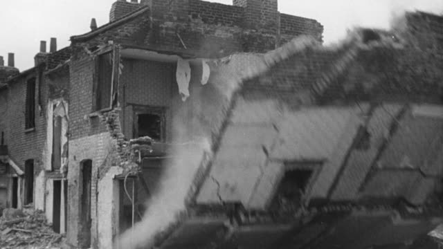 1940 MONTAGE Sledgehammer breaking through old brick wall, deconstruction worker running away from collapsing building wall, and exterior view of large new housing complex / United Kingdom