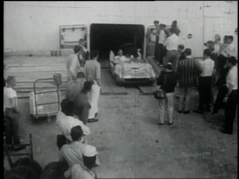1957 ws sleek car leaves garage and enters raceway near a crowd of onlookers / nassau, bahamas - 1957 stock videos & royalty-free footage
