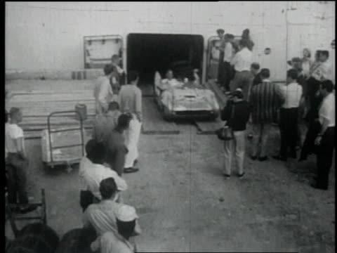 vídeos de stock e filmes b-roll de 1957 ws sleek car leaves garage and enters raceway near a crowd of onlookers / nassau, bahamas - 1957