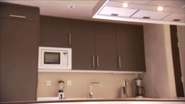 a sleek modern kitchen features brown cabinets. - microwave stock videos & royalty-free footage