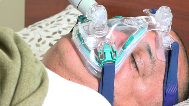 sleep apnea: obese man wearing cpap mask as he sleeps - sleep apnea stock videos and b-roll footage