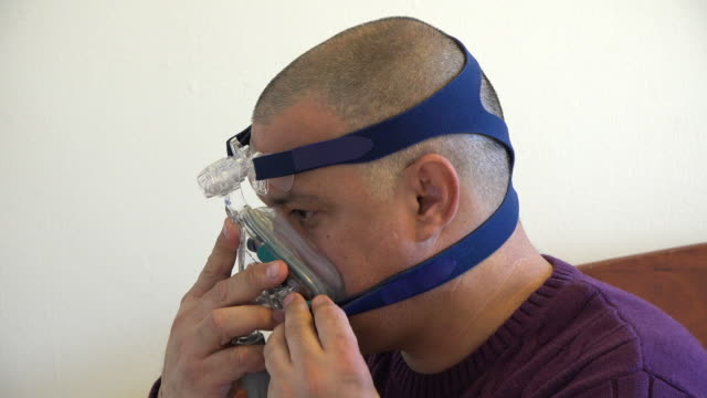 sleep apnea: person wearing a cpap mask - sleep apnea stock videos and b-roll footage