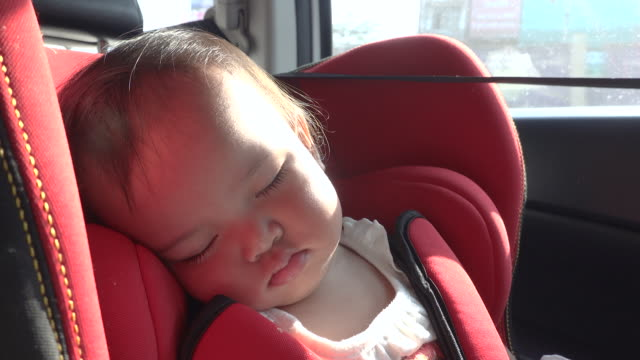 sleeping baby girl on red car safety seat - reclining stock videos & royalty-free footage