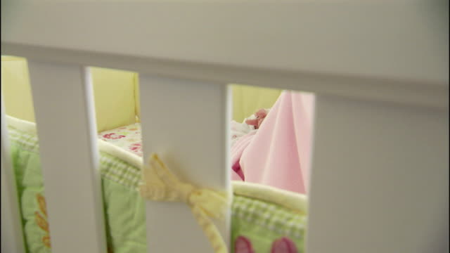 a sleeping baby stirs in her crib near a bassinet and a baby monitor on a table. - nursery bedroom stock videos & royalty-free footage