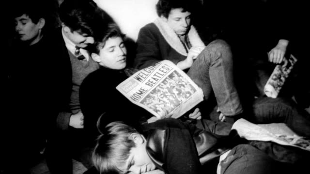 vídeos de stock e filmes b-roll de sleeping girls piled up on floor wait for the beatles to arrive at heathrow airport / 'welcome home beatles' sign / newspaper on top of sleeping boy... - celebridade