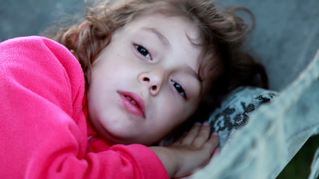 sleeping little girl wakes up and looks at camera - svegliarsi video stock e b–roll