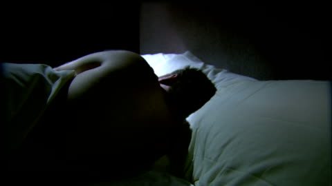 a sleeping man turns on a bed in a dark room. - sleeping stock videos & royalty-free footage