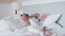 Sleeping Senior Couple Lying In Bed At Home Together