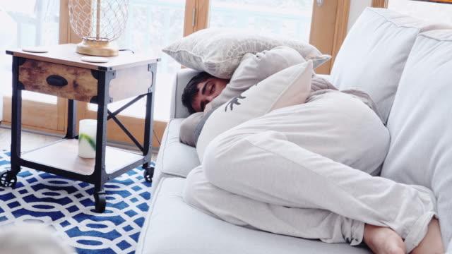 vídeos de stock e filmes b-roll de sleeping under the mountain of cushions in living room couch - life during covid-19 quarantine - almofada roupa de cama