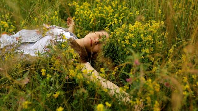 stockvideo's en b-roll-footage met slapende jonge vrouw met bloemen in haar zak - generation z